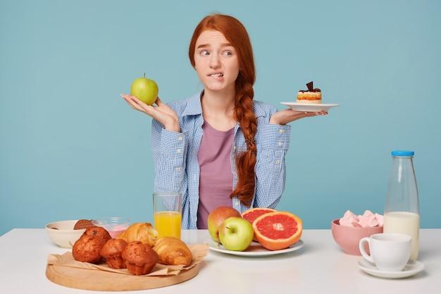 Porträt der schönen fitnessfrau in der sportkleidung, die versucht, zwischen gesundem und ungesundem essen zu wählen