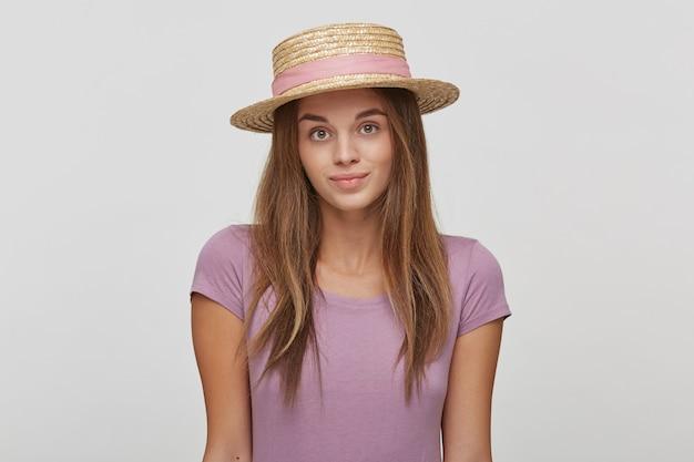 Porträt der schönen fleißigen brünetten frau in einem strohhut mit einem rosa band
