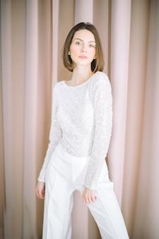 Porträt der schönen frau am raum mit der perle, die im weißen hemd und in der hose steht und schaut