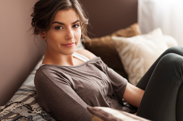 Porträt der schönen frau, die auf sofa entspannt