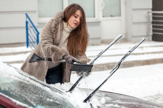 Porträt der schönen frau, die auto mit bürste nach schneesturm säubert