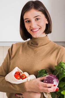 Porträt der schönen frau, die bio-gemüse hält
