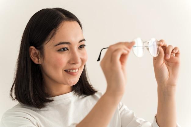Porträt der schönen frau, die die sauberkeit der brille überprüft, während sie sie hält und darauf schaut. mädchen posiert auf einem weißen wandhintergrund