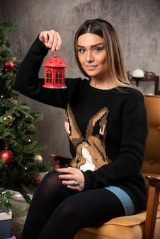 Porträt der schönen frau, die ein weihnachtspavillonspielzeug hält. hochwertiges foto
