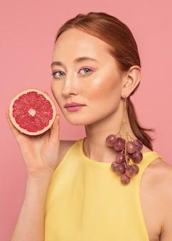Porträt der schönen frau, die eine frucht hält