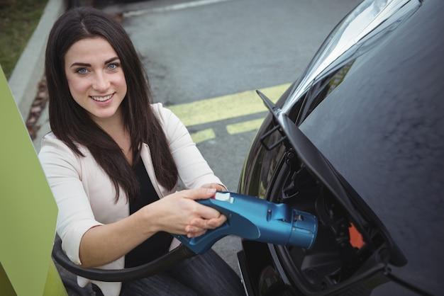 Porträt der schönen frau, die elektroauto auflädt