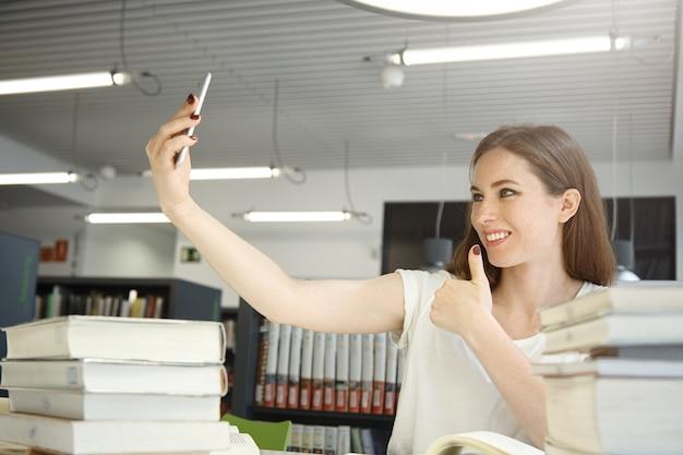 Porträt der schönen frau, die handy hält, ein selfie gegen bibliotheksinnenraum nimmt, frau, die glücklich schaut, lächelt und mit daumen hoch posiert, umgeben von büchern und handbüchern