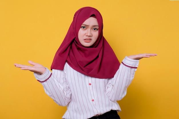 Porträt der schönen frau, die hijab trägt, zeigt etwas auf ihrer hand verwirrenden ausdruck
