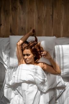 Porträt der schönen frau, die im bett auf boden vertikal schläft