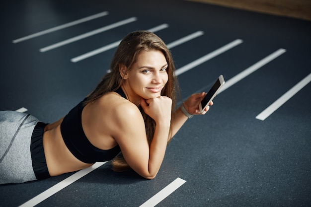 Porträt der schönen frau, die im fitnessstudio nach einem harten training unter verwendung eines smartphones liegt, um fotos zu den sozialen medien zu posten.