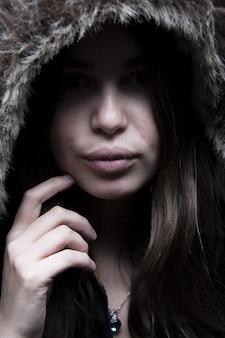 Porträt der schönen frau, die in der schwarzen jacke mit der haarigen kapuze steht und schaut