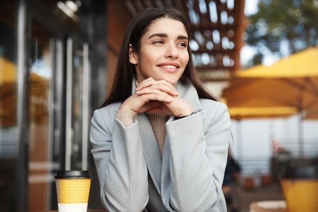 Porträt der schönen frau, die in einer cafeteria trinkt.