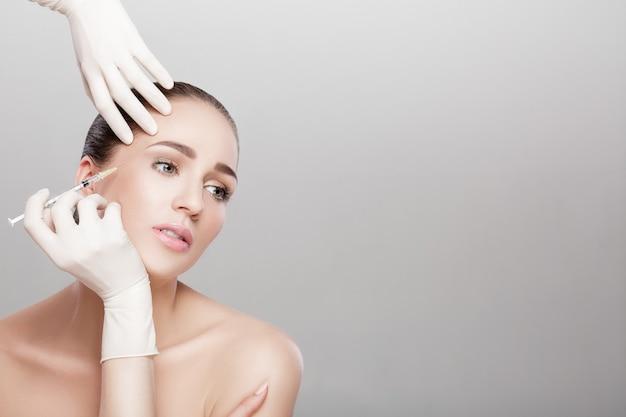 Porträt der schönen frau, die injektion erhält. schönheitsspritzen und kosmetik