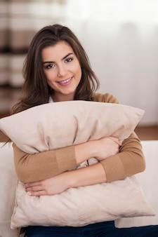 Porträt der schönen frau, die kissen auf sofa umarmt