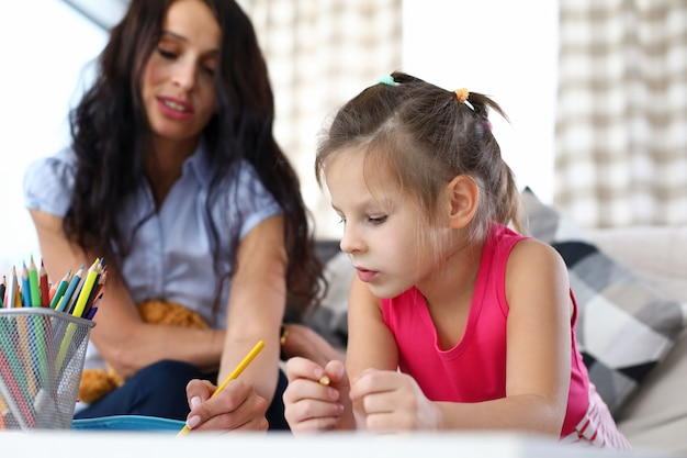 Porträt der schönen frau, die kleines kind hilft. glückliche lächelnde mutter, die freizeit mit tochter zu hause genießt. mutterschafts- und kindheitskonzept