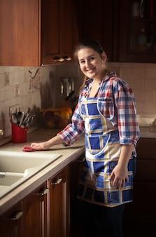 Porträt der schönen frau, die küchentisch säubert