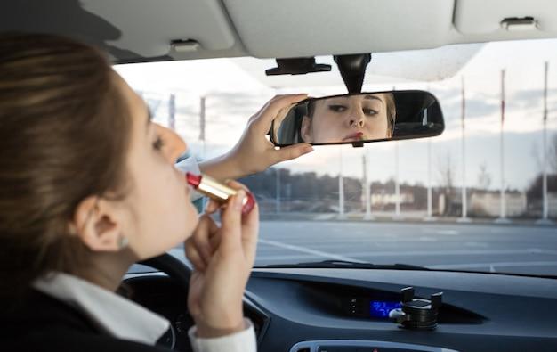 Porträt der schönen frau, die lippenstift im auto aufträgt