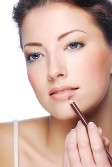 Porträt der schönen frau, die lippenstift unter verwendung des lippen-concealer-pinsels anwendet