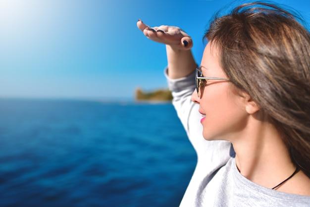 Porträt der schönen frau, die mit der hand in der stirn und im meer nach vorne schaut