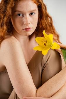 Porträt der schönen frau, die mit frühlingsblume aufwirft