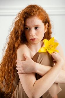 Porträt der schönen frau, die mit herrlicher frühlingsblume aufwirft