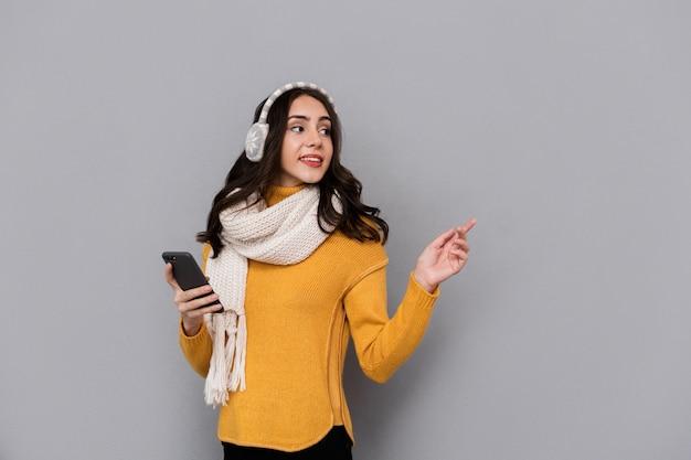 Porträt der schönen frau, die ohrenschützer und schal unter verwendung des mobiltelefons trägt, lokalisiert über grauem hintergrund