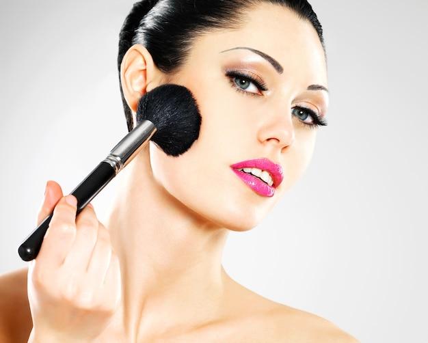 Porträt der schönen frau, die rouge auf gesicht mit kosmetikpinsel aufträgt