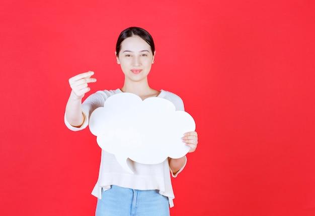 Porträt der schönen frau, die sprechblase mit einer wolkenform hält