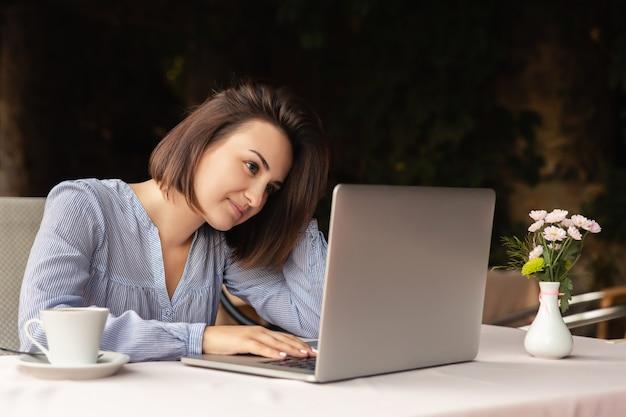 Porträt der schönen frau, die von zu hause aus arbeitet, sitzt sie mit einer tasse kaffee am tisch und arbeitet drinnen am laptop