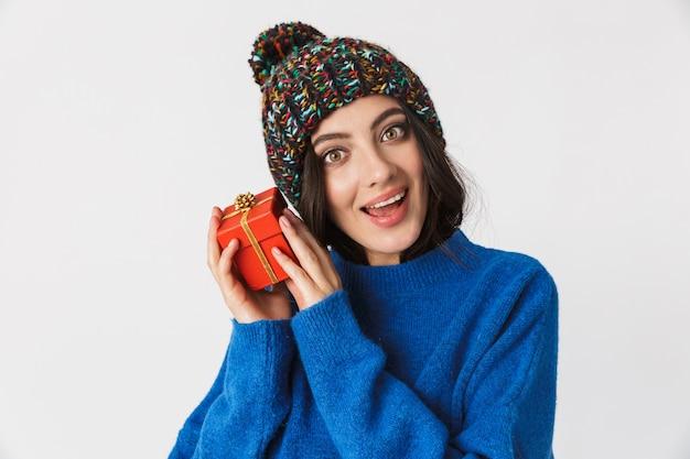 Porträt der schönen frau, die wintermütze hält geschenkbox während des stehens trägt, lokalisiert auf weiß