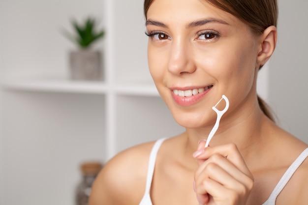 Porträt der schönen frau, die zähne mit zahnseide reinigt.