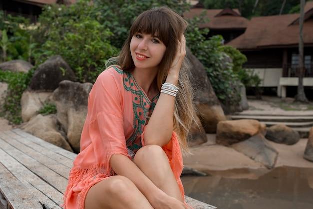 Porträt der schönen frau im boho-kleid, das nahe luxusresort aufwirft. genießender urlaub auf tropischer insel.
