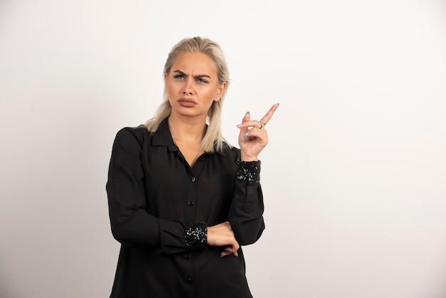 Porträt der schönen frau im schwarzen hemd, das auf weißem hintergrund aufwirft. hochwertiges foto