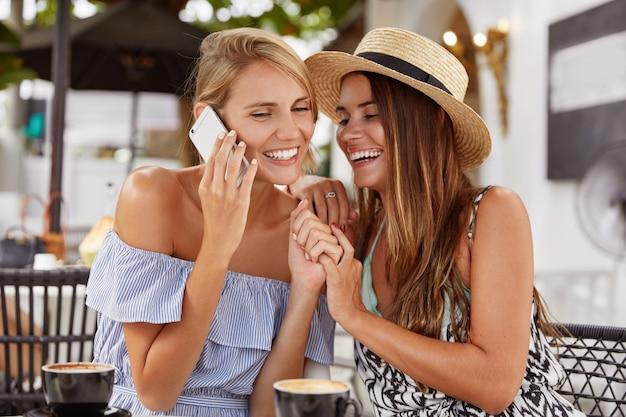Porträt der schönen frau in der sommerbluse, spricht per handy, freut sich, jemanden zu hören, hält hände mit freundin, hat spaß zusammen im café, trinkt aromatischen cappuccino, lacht freudig