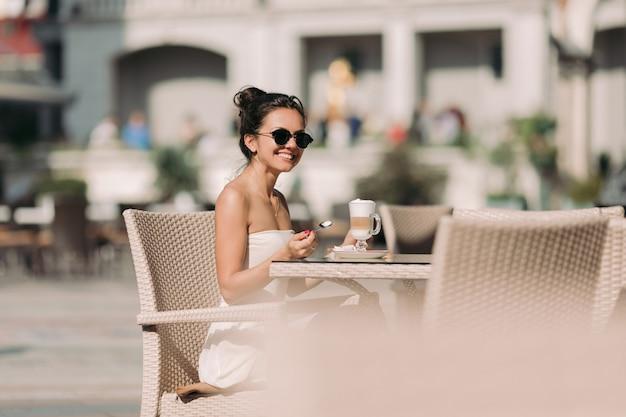 Porträt der schönen frau in der sonnenbrille und im kleid, die in einem café sitzen und kaffee an einem sonnigen sommertag trinken.