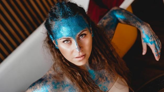 Porträt der schönen frau mit blauen glitzern auf ihrem gesicht. das konzept der freaks und aliens. menschen sind anders als andere. individualität