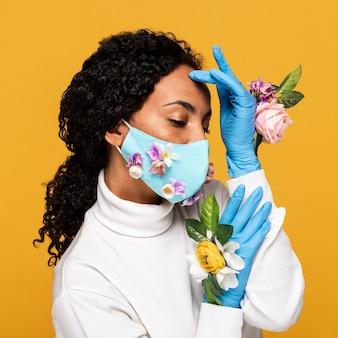 Porträt der schönen frau mit blumenhandschuhen und maske