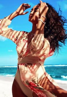 Porträt der schönen frau mit dem dunklen langen haar im beige kleid, das am sommerstrand aufwirft