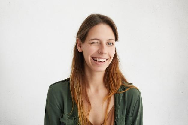 Porträt der schönen frau mit dem langen haar, das zwinkert, während gute laune lächelnd ihre weißen perfekten zähne zeigt.