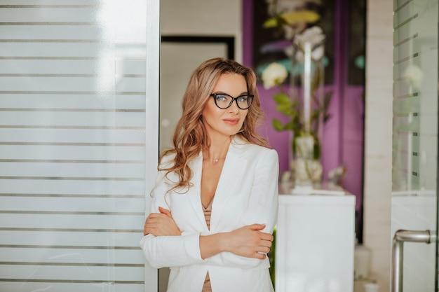 Porträt der schönen frau mit dem langen lockigen haar in der weißen bürojacke, die mit brille im schrank aufwirft
