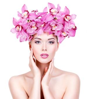 Porträt der schönen frau mit den rosa blumen. hübsches erwachsenes mädchen mit gesunder haut eines gesichts. - isoliert auf weißer wand
