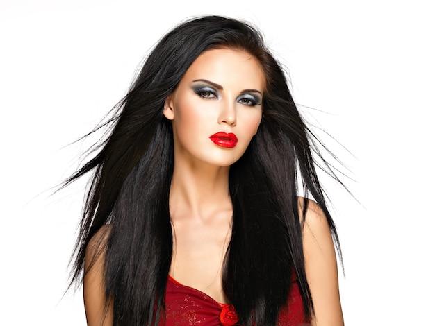 Porträt der schönen frau mit den schwarzen glatten haaren und den roten lippen, abendmake-up. hübsches modell, das im studio aufwirft