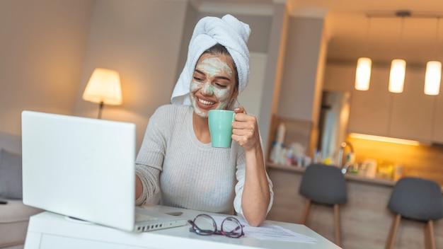 Porträt der schönen frau mit gesichtsmaske, die einen kaffee zu hause nimmt