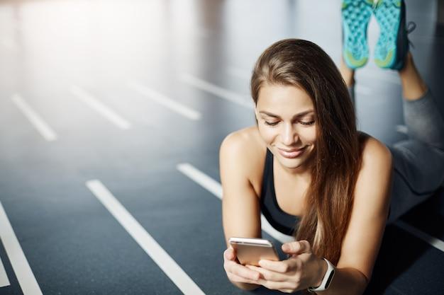 Porträt der schönen frau mit handy und fitness-tracker im fitnessstudio, um ihr gewicht und kalorienverbrauch zu verfolgen. gesundes lebenskonzept.
