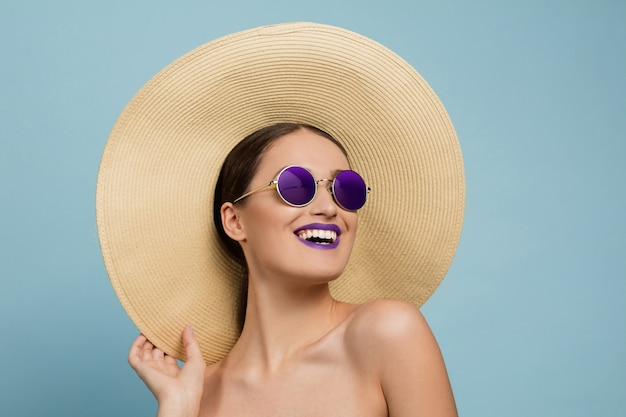 Porträt der schönen frau mit hellem make-up, hut und sonnenbrille auf blauem studio