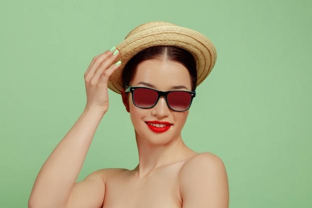 Porträt der schönen frau mit hellem make-up, hut und sonnenbrille auf grünem studiohintergrund. stilvolle und modische marke und frisur. farben des sommers. beauty-, mode- und anzeigenkonzept. lächelnd.