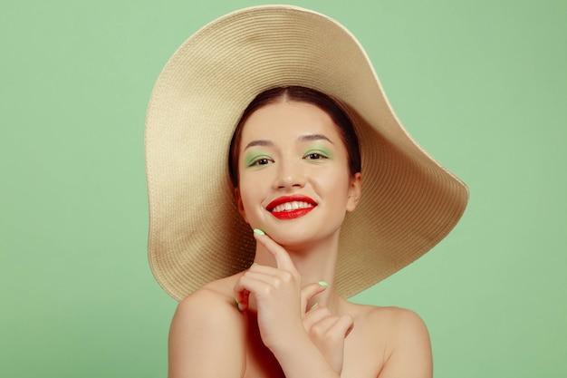 Porträt der schönen frau mit hellem make-up und hut auf grünfläche. stilvolle und modische marke und frisur. farben des sommers
