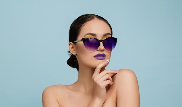 Porträt der schönen frau mit hellem make-up und sonnenbrille auf blauem studiohintergrund. stilvolle, modische marke und frisur. farben des sommers. beauty-, mode- und anzeigenkonzept. ernst, zuversichtlich.