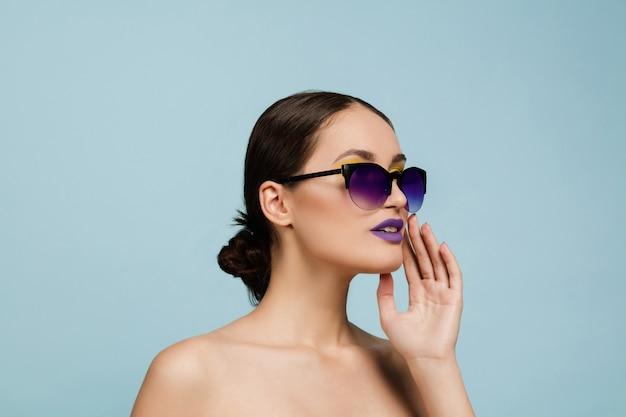 Porträt der schönen frau mit hellem make-up und sonnenbrille auf blauem studiohintergrund. stilvolle, modische marke und frisur. farben des sommers. beauty-, mode- und anzeigenkonzept. jemanden anrufen.