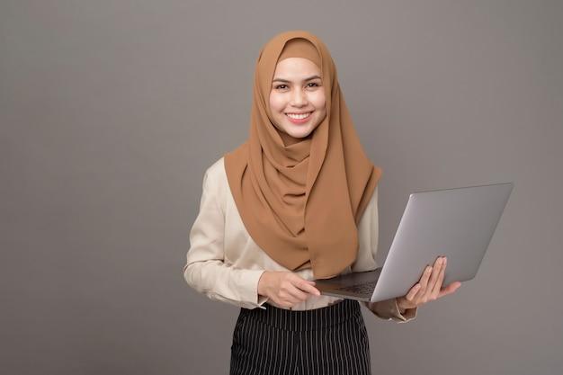 Porträt der schönen frau mit hijab hält computer-laptop auf grau